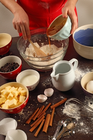 messy kitchen: Photo of a female mixing ingredients in a large glass bowl.