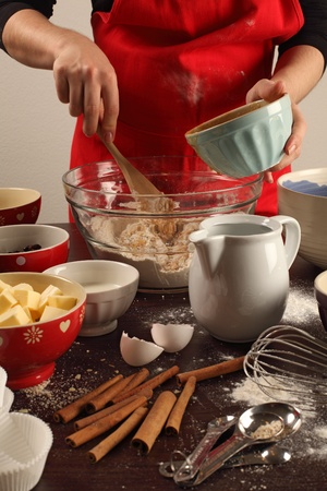 messy kitchen: Photo of a female mixing ingredients in a large glass bowl. Could be muffins, cookies, bread, etc.