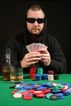 Photo of a hooded man playing poker while wearing sunglasses. Playing cards have been altered to be generic. photo