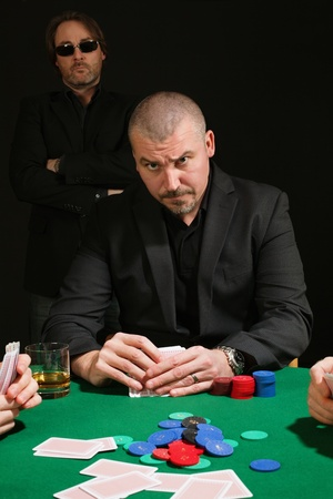card player: Photo of a very serious poker player staring across the table. Cards have been altered to be generic.