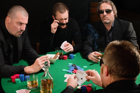 casino table: Photo of three male poker players staring across in anger at the fourth player. Cards have been altered to be generic.