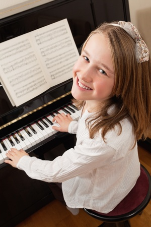 young musician: Photo of a young girl playing the piano at home. Sheet music has been altered to be unrecognizable.