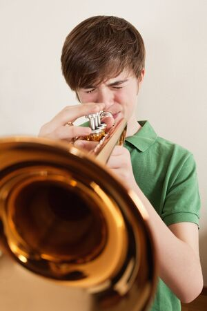 brass instrument: Photo of a young teen playing his gold trumpet.