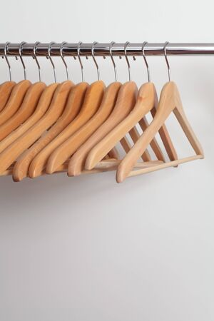 closet rod: Photo of empty wooden clothes hangers in a retail store. Stock Photo