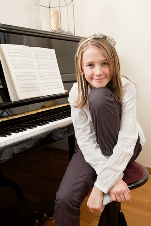 Photo of a young happy girl sitting in front of her piano. Sheet music has been altered to be unrecognizable. photo