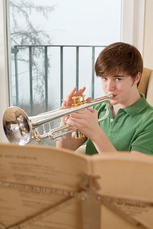 trompette: Photo d'un homme chez les adolescentes � pratiquer sa trompette � la maison. Banque d'images