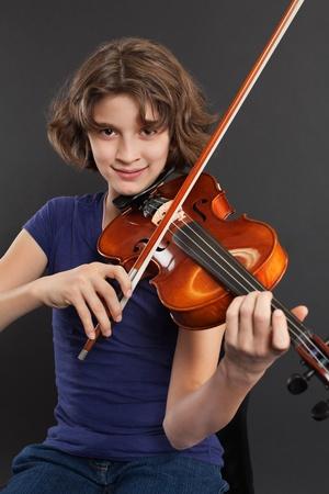 violines: Foto de una joven practicando el viol�n sobre un fondo oscuro. Foto de archivo