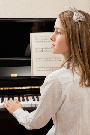 Photo of a young girl playing the piano at home. Sheet music has been completely altered to be unrecognizable. photo