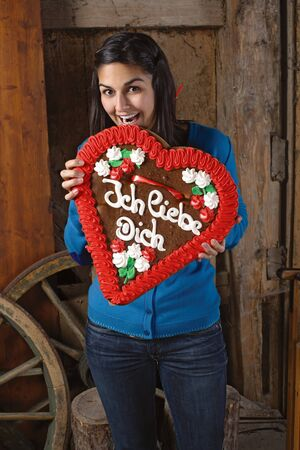 in liebe: Photo of a beautiful female excited to eat her giant heart-shaped gingerbread cookie with Ich Liebe Dich written across. Stock Photo