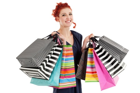 shopaholics: A very happy shopaholic girl holding many shopping bags and smiling about her rabid purchases.