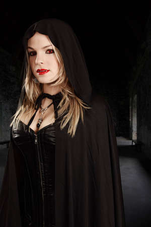 female vampire: Photo of a female vampire dressed in leather corset and hooded cape. Stock Photo