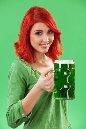 Photo of a beautiful redhead holding a huge mug of green beer for St. Patricks Day celebrations.