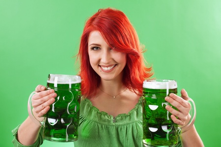 Photo of a beautiful redhead holding two huge mugs of green beer for St. Patricks Day celebrations. photo