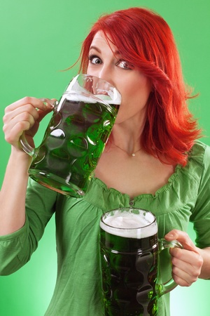 Photo of a beautiful redhead holding two huge mugs of green beer and drinking from one, on St. Patricks Day. photo