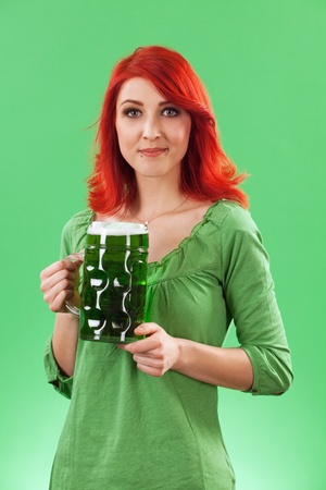 Photo of a beautiful redhead holding a huge mug of green beer on St. Patricks Day. photo