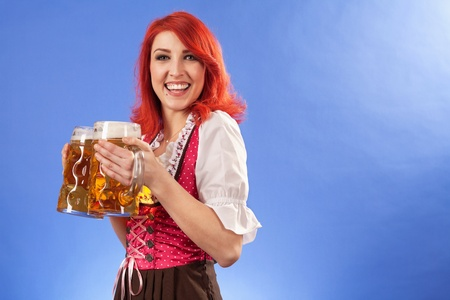 Photo of a beautiful female waitress wearing traditional dirndl and holding two mass beer steins. photo