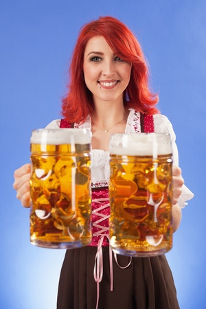steins: Photo of a beautiful female waitress wearing traditional dirndl and holding two mass beer steins. Stock Photo