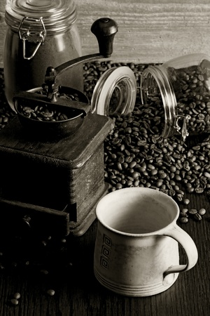 Photo of roasted coffee beans, coffee cup, antique grinder on a wooden table. photo