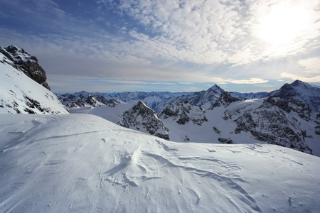 steep cliff: View of the snowy peaks of the Swiss Alps while standing on Titlis. Stock Photo