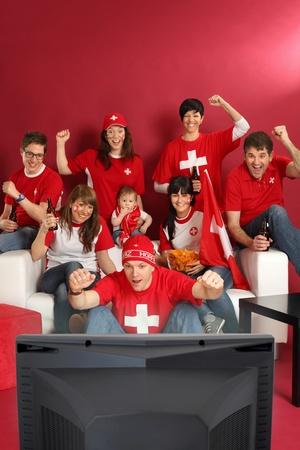 Photo of Swiss sports fans watching television and cheering for their team. Plenty of copyspace. photo