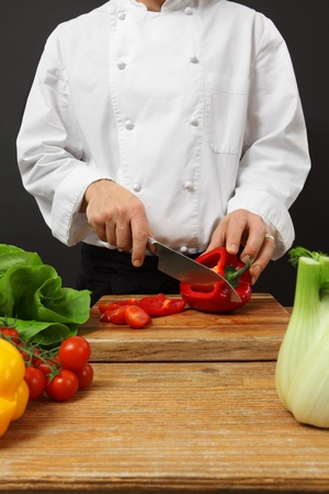 chopping: Photo of a chef chopping vegetables on a wooden cutting board.