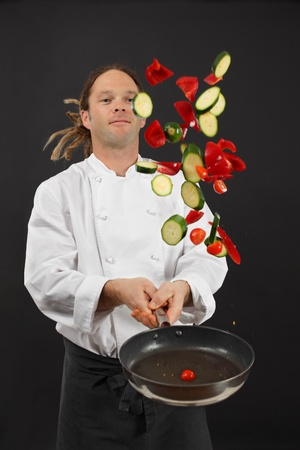 Photo of a young chef with dreadlocks tossing chopped vegetables in the air from a frying pan. photo