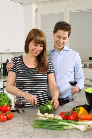 Photo of a young couple preparing salad in their kitchen and drinking wine. Stock Photo - 13275154