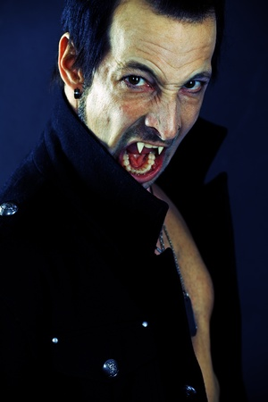 Photo of a male vampire with mouth open and fangs showing.  Harsh lighting and heavily filtered for scarier feel.