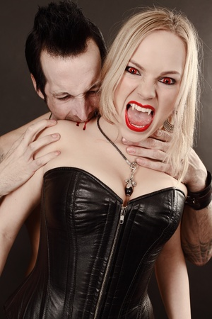 mordendo: Photo of a female vampire with mouth open and fangs showing being bitten by male vampire.  Desaturated to create pale skin.