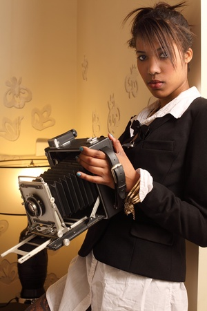 african fashion: Photo of a beautiful young woman of African descent, holding a vintage 4x6 film camera.