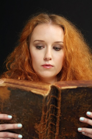 Photo of a beautiful redhead female reading an old bible from 1786  photo