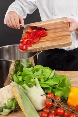 Foto de un chef poner las verduras picadas en una cacerola grande. Foto de archivo