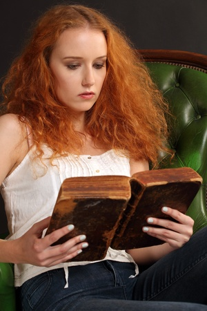 Photo of a beautiful redhead female reading an old bible from 1786. photo