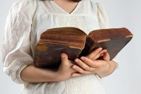 Photo of a female holding an open bible from 1786 in her hands. photo