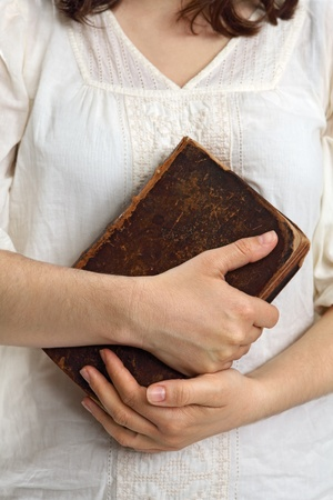 holding bible: Photo of a female holding an old bible or book in her hands. Stock Photo