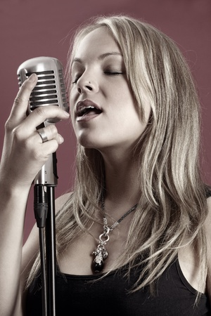Photo of a beautiful young blond singing into a vintage microphone. Desaturated and stylized for the utmost coolness. photo