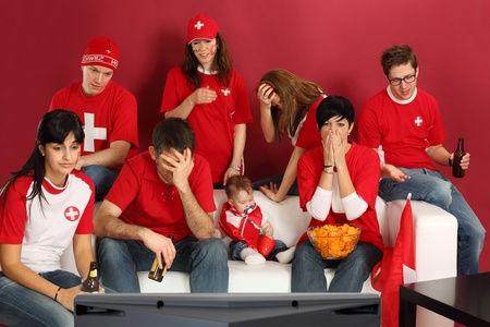 sports fans: Photo of Swiss sports fans watching television and being disappointed with the game. Stock Photo