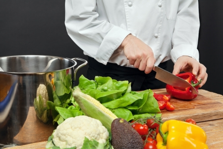 Photo of a chef chopping vegetables on a wooden cutting board. photo