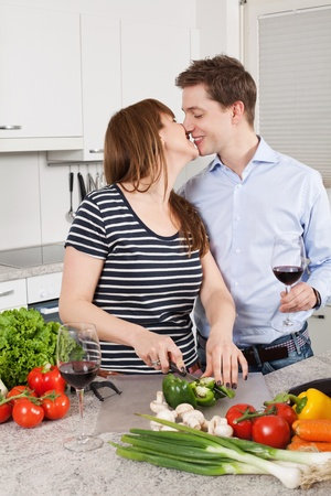 Photo of a young couple preparing salad in their kitchen and drinking wine. photo