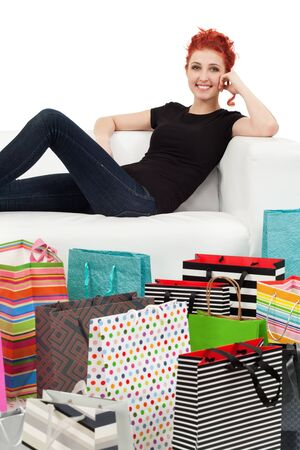 A happy shopping girl sitting on a white couch surrounded with shopping bags. Stock Photo - 13785755