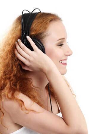 Photo of the side-view of a beautiful redhead listening to music with her headphones. photo