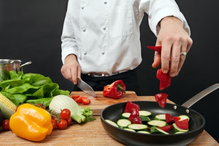 Photo of a chef adding chopped vegetables to a pan. photo