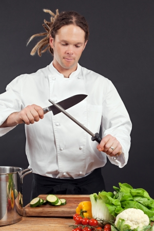sharpener: Photo of a chef with dreadlocks sharpening his chopping knife. Stock Photo