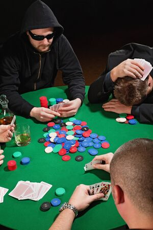 four people: Photo of four men playing poker with one player frustrated. Focus is on the winning poker hand.