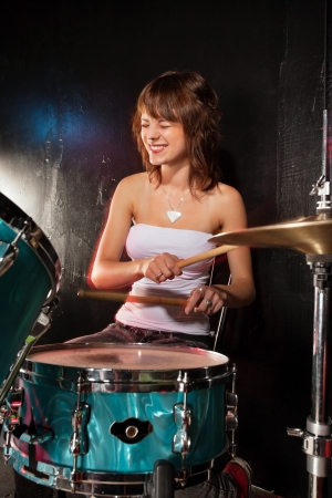 drummer: Photo of a female drummer playing a drum set on stage.