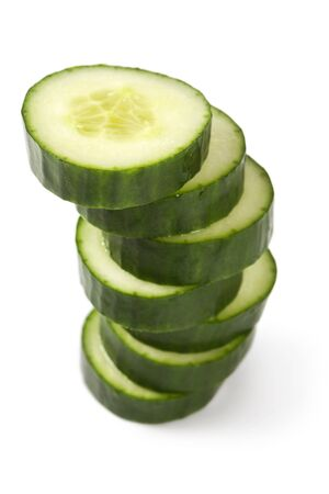 cucumber slice: A cucumber cut into thick slices and stacked over a white background.