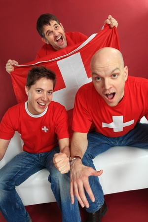 Photo of three male Swiss sports fans cheering for their team. photo
