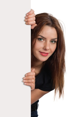 Photo of a young brunette female peeking out from behind a sign.