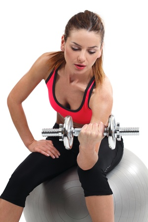 curls: an attractive female doing dumbbell curls while sitting on an exercise ball. Stock Photo