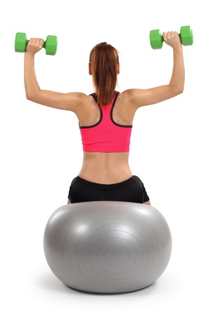 gym ball: a female from behind doing dumbbell shoulder press while sitting on an exercise ball.